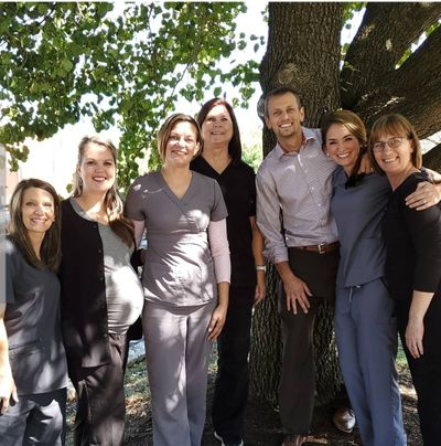 Group photo of our dental staff standing under a tree outdoors